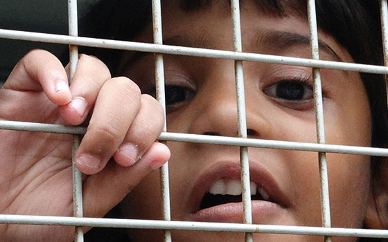 Child behind cage